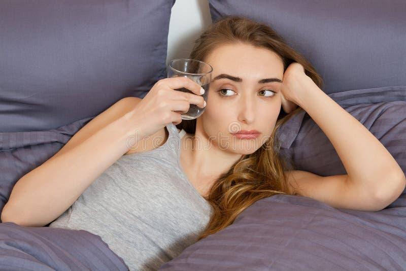 El sentirse mal de una resaca por la mañana: vaso de agua del control de la mujer joven y mentira en dormitorio de la cama fotografía de archivo libre de regalías