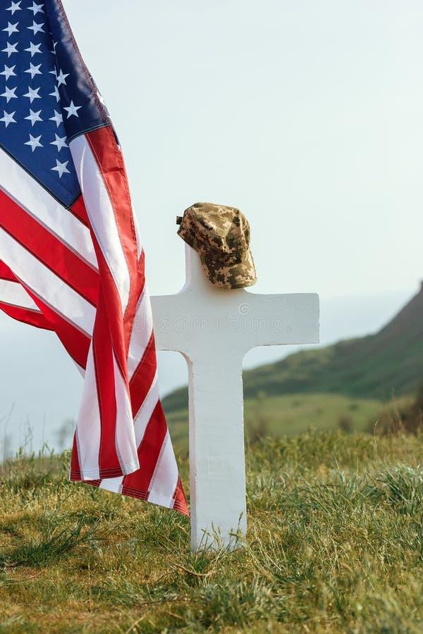 El sepulcro de un soldado Bandera americana sobre el sepulcro del soldado difunto En el sepulcro un casquillo militar imagenes de archivo
