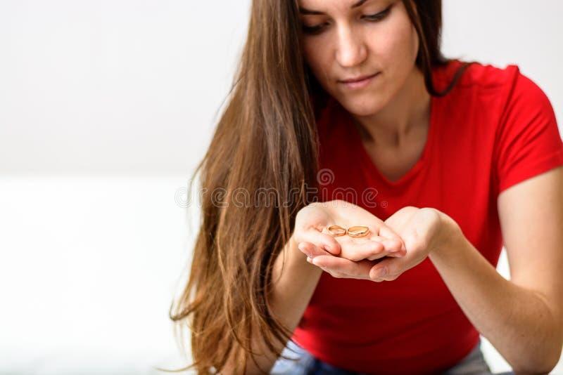El ser esposa triste mira el anillo en la palma delante de él, nostálgico sobre un marido anterior, familia, boda El concepto de  imagen de archivo