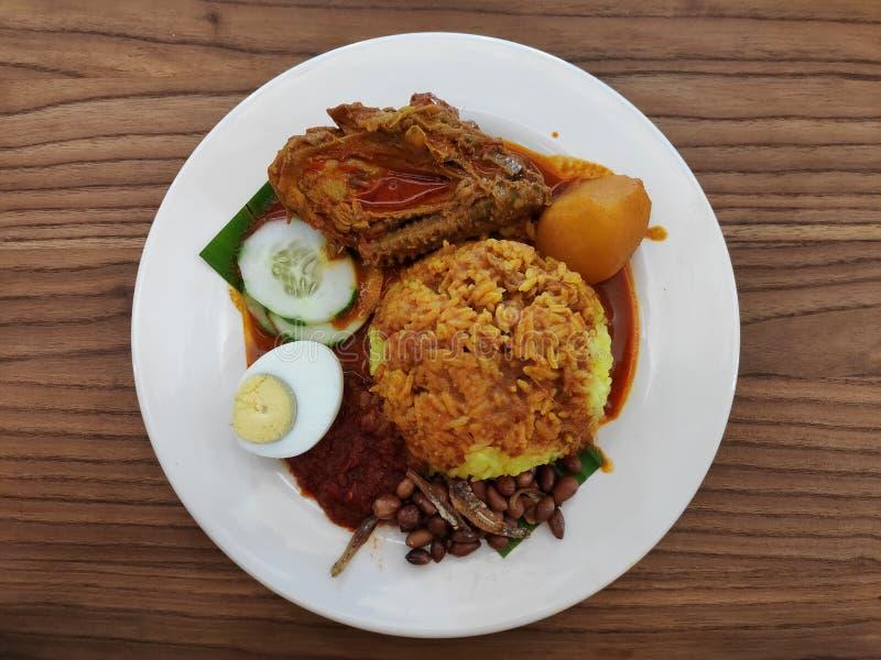 El servicio de Nasi Lemak con el curry del pollo, huevo, pepino cortó, las anchoas, nuez de tierra y sambal fotografía de archivo libre de regalías