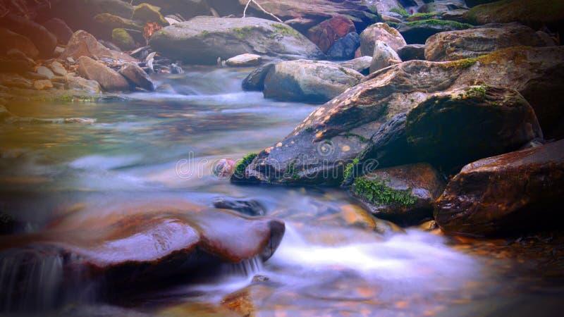 El Shinning colorido de la luz del sol mágica de la fantasía sobre una cala o un río en las montañas ahumadas foto de archivo