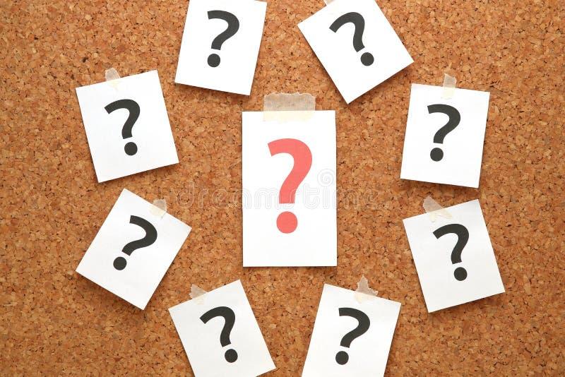 El signo de interrogación rojo en un trozo de papel y muchos signos de interrogación en corcho suben imagenes de archivo