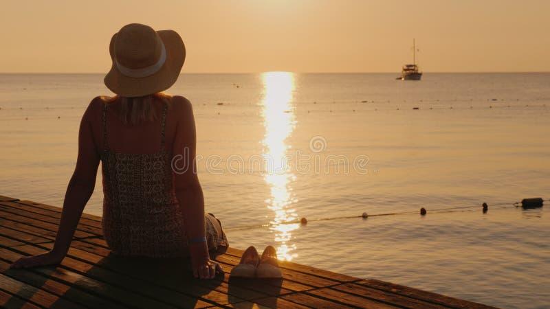 El silencio y la pacificación en la madrugada en el embarcadero del mar, la muchacha disfruta de soledad imagen de archivo libre de regalías