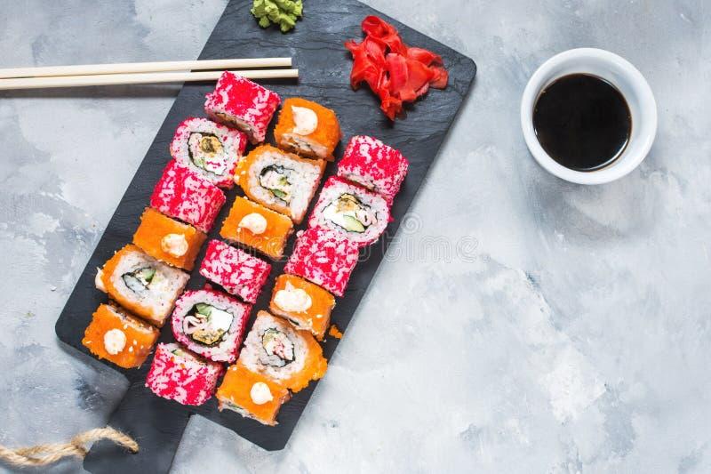 El sistema clasificado de los rollos de sushi sirvió en la placa en fondo concreto imágenes de archivo libres de regalías