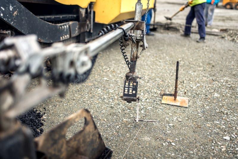 El sistema de dirección de maquinaria de asfaltado, asfalto industrial acoda fotografía de archivo