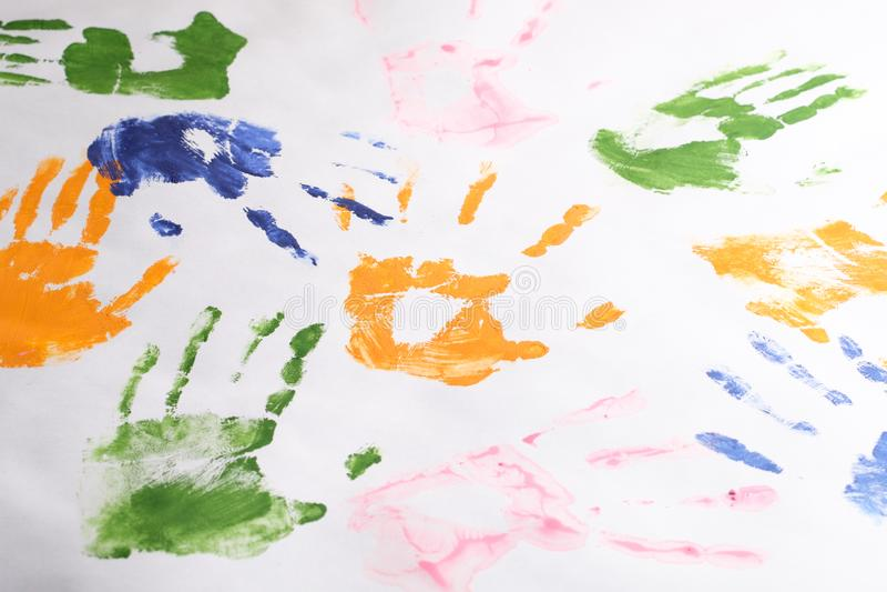 El sistema de handprints de niños se fue con las pinturas coloridas en un fondo blanco, creatividad del ` s de los niños fotografía de archivo