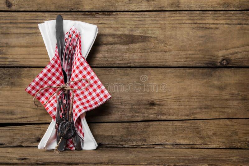 El sistema de la bifurcación y del cuchillo con blanco rojo comprobó la servilleta en viejo w rústico foto de archivo