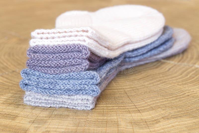 El sistema de pequeña diversa cachemira coloreada linda hizo punto calcetines recién nacidos del bebé en un fondo de madera del e fotos de archivo libres de regalías