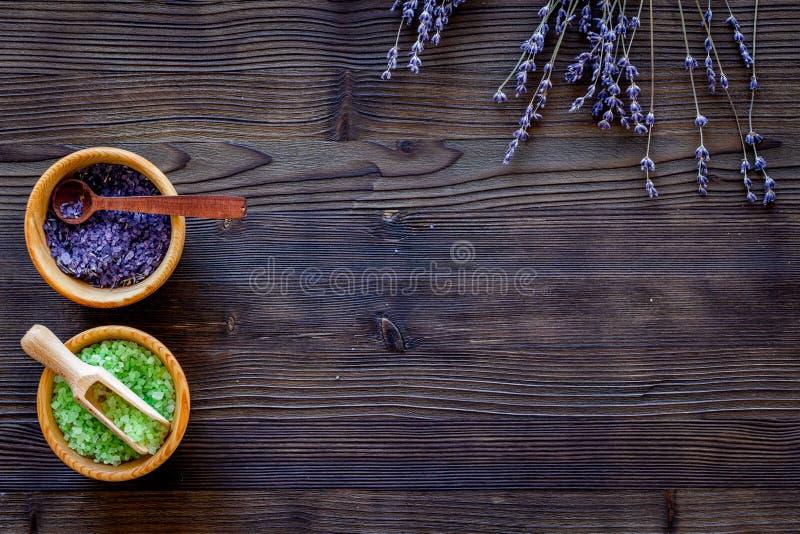El sistema del cosmético con las hierbas de la lavanda y la sal del mar en cuenco en plano de madera del fondo de la tabla ponen  imágenes de archivo libres de regalías