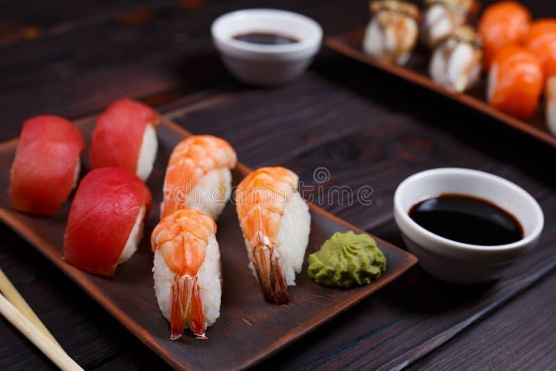 El sistema del sushi de Nigiri con el atún y las gambas sirvió en las placas de la arcilla, clo imagen de archivo