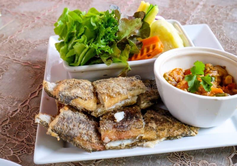 El sistema tailandés de la goma del chile sirvió con los pescados y la verdura fritos salados fotografía de archivo