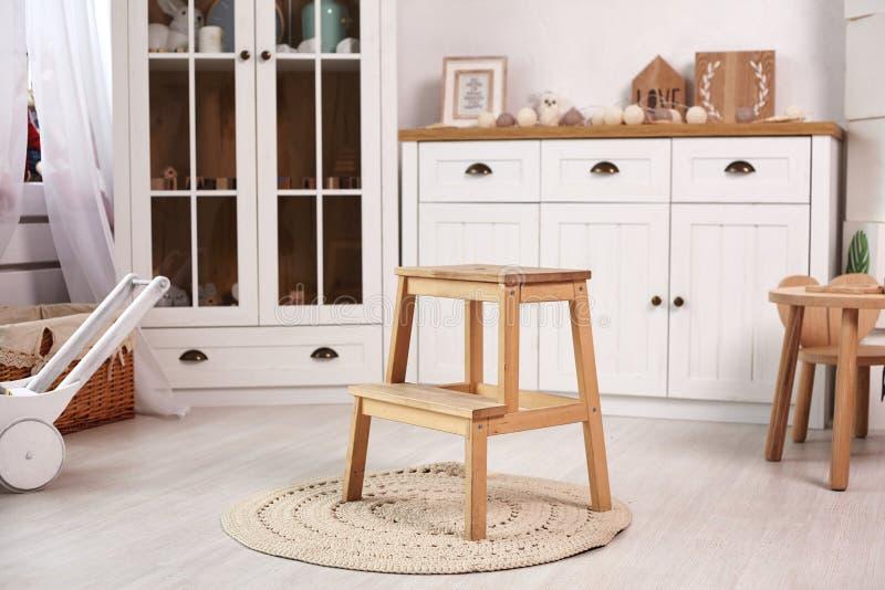 El sitio del ni?o elegante con muebles de madera blancos y una ventana imagenes de archivo