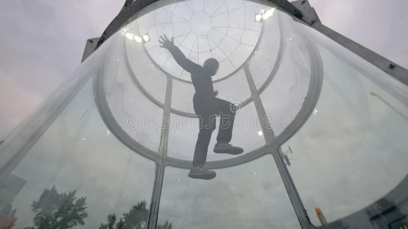 El skydiver del hombre vuela en túnel de viento Túnel de viento que salta en caída libre interior foto de archivo