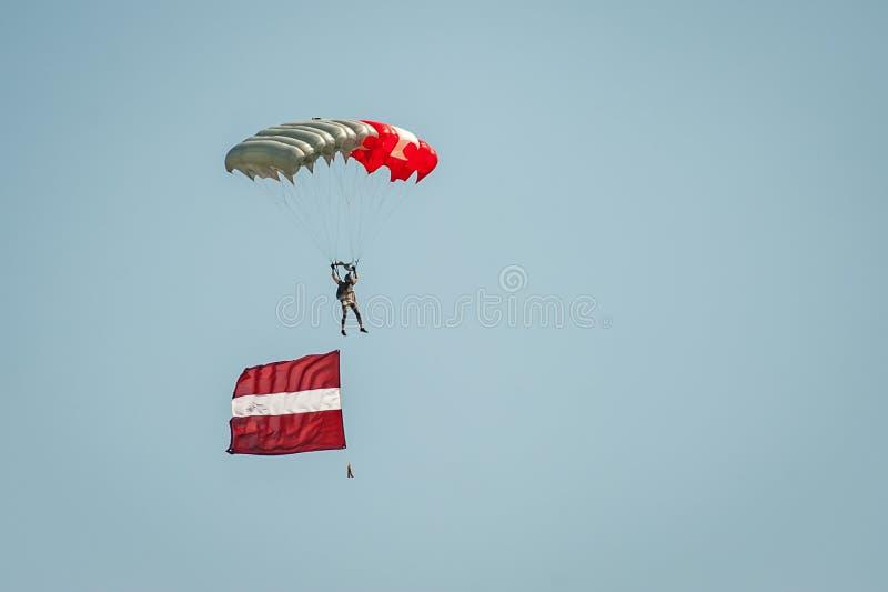 El Skydiver viene abajo del cielo en un ala flexible con la bandera letona Aterrizaje del paracaidista fotografía de archivo
