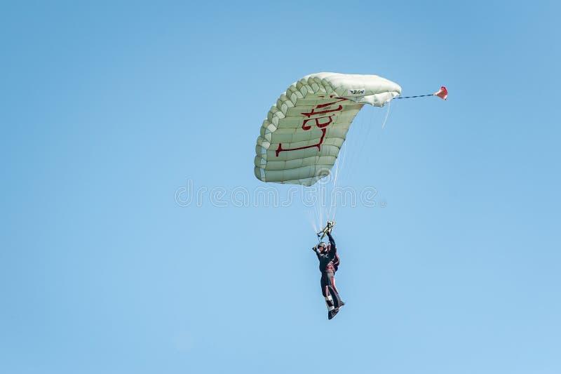 El Skydiver viene abajo del cielo en un ala flexible con la inscripción Letonia Aterrizaje del paracaidista fotos de archivo