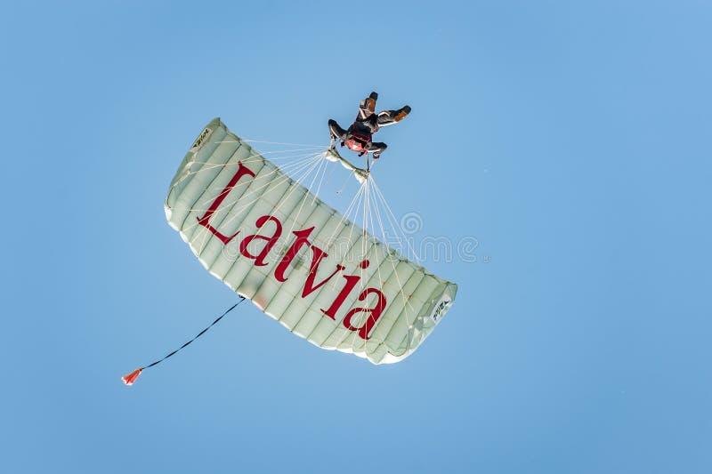 El Skydiver viene abajo del cielo en un ala flexible con la inscripción Letonia Aterrizaje del paracaidista imágenes de archivo libres de regalías