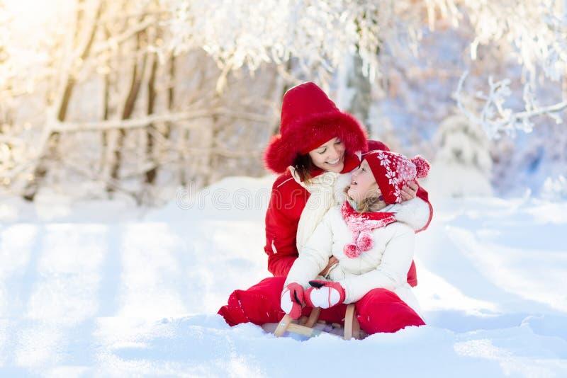 El sledding de la madre y del niño Diversión de la nieve del invierno Familia en trineo imagen de archivo libre de regalías