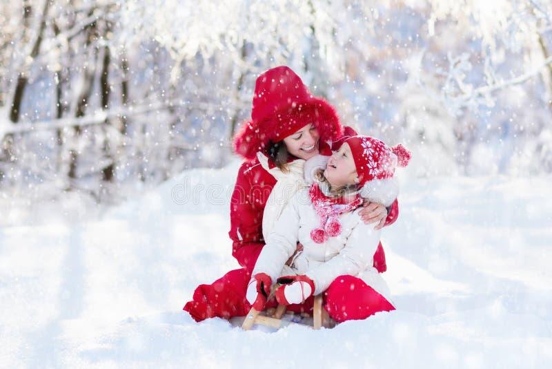 El sledding de la madre y del niño Diversión de la nieve del invierno Familia en trineo imagen de archivo