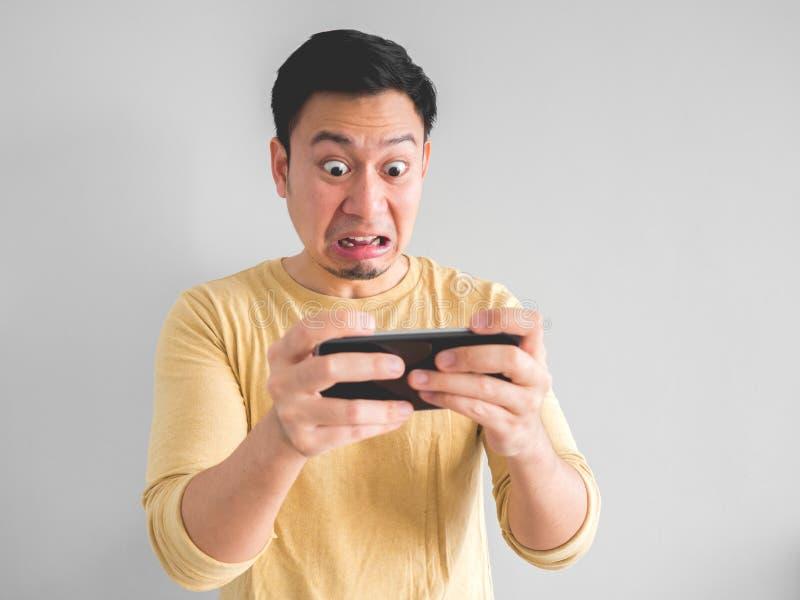 El smartphone de los juegos del hombre siente chocado fotos de archivo libres de regalías