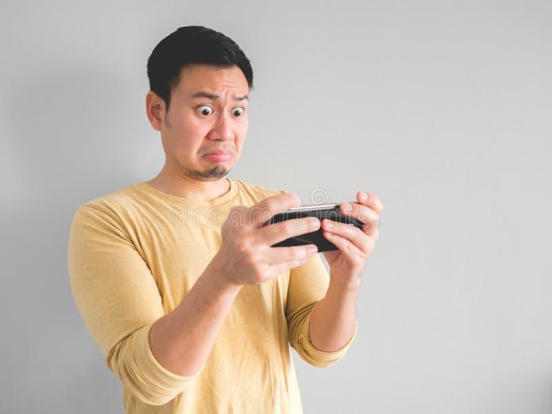 El smartphone de los juegos del hombre siente chocado foto de archivo