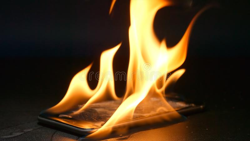 El smartphone roto está quemando en una tabla fotografía de archivo