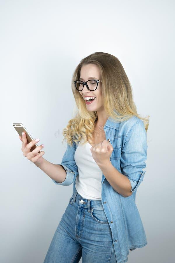 El smartphone rubio joven hermoso de la tenencia de la mujer mira cierre feliz encima del fondo blanco imagen de archivo