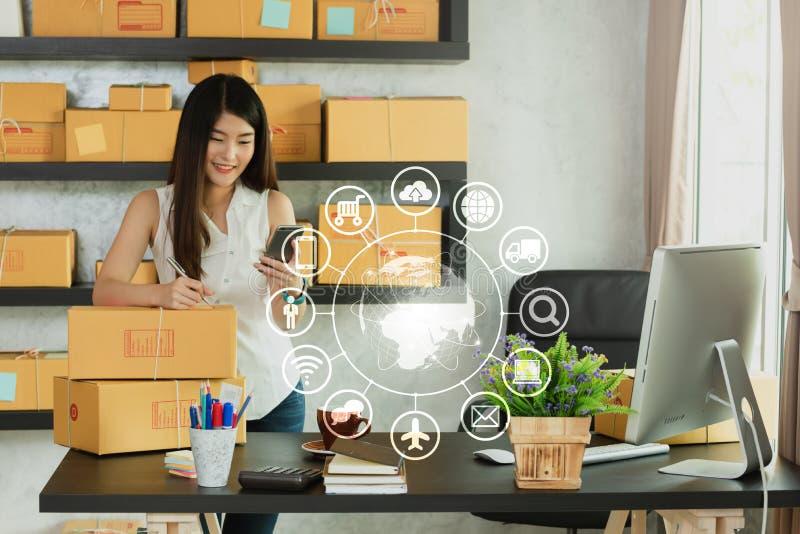 El smartphone y el ordenador port?til asi?ticos jovenes del uso de la mujer corren propio negocio en imagen de archivo libre de regalías