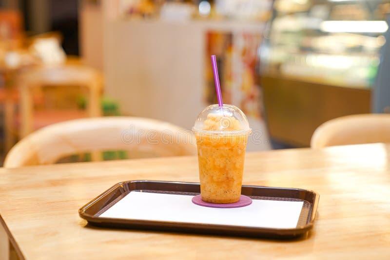 El smoothie de la fruta de la pasión del plástico se lleva la taza en el restaurante imágenes de archivo libres de regalías