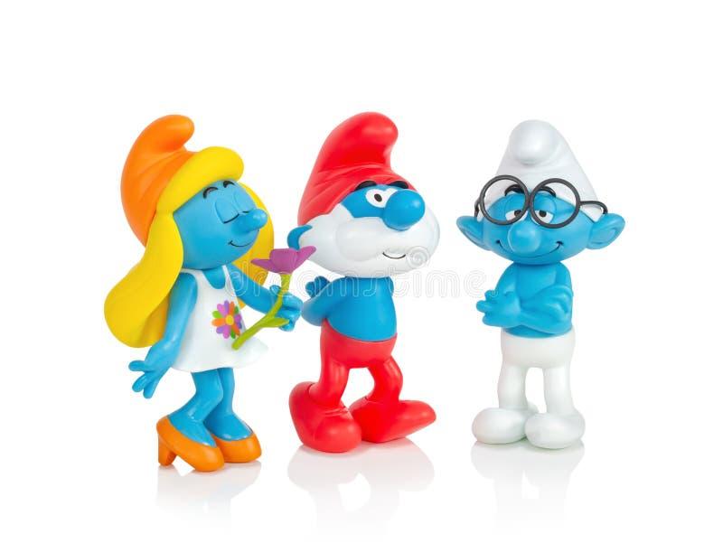 El Smurfs - el Smurfette, el Pappa Smurf y los juguetes inteligentes aislados en el fondo blanco con la reflexión de la sombra Fi imagenes de archivo