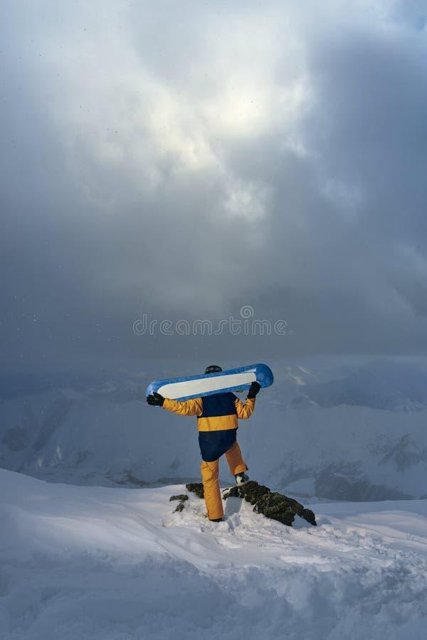 El Snowboarder coloca el acantilado y tablero el sostenerse en sus hombros imagen de archivo