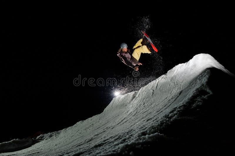 El snowboarder de Freeride con los dreadlocks está saltando en nieve del polvo en la noche imagenes de archivo