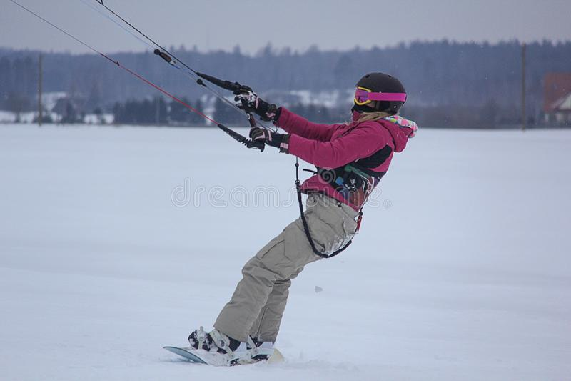 El Snowboarder de la muchacha monta con la cometa Snowkiting en invierno fotos de archivo libres de regalías