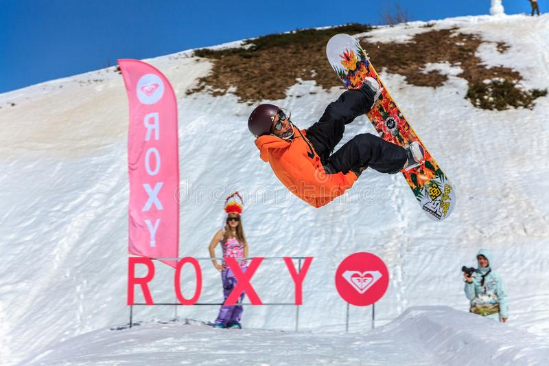 El snowboarder de la mujer vuela de un salto en el fondo nevoso de la cuesta de las montañas del Cáucaso del invierno imágenes de archivo libres de regalías