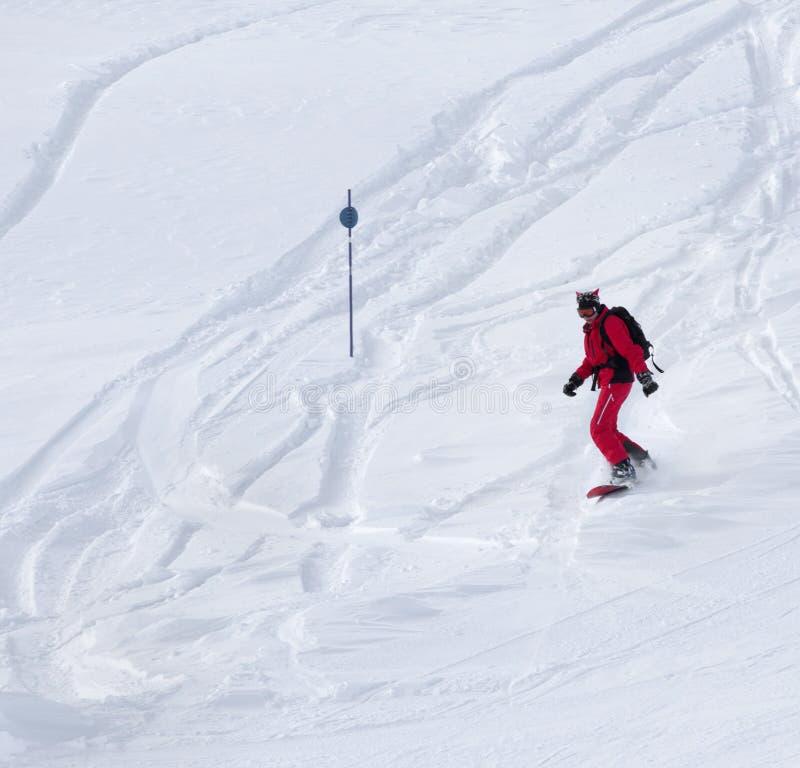 El Snowboarder desciende en cuesta fuera de pista nevosa imagen de archivo