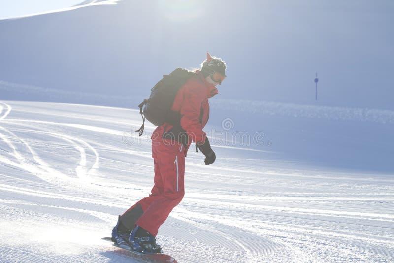 El Snowboarder desciende en la cuesta nevosa del esquí preparada por la máquina de la preparación imágenes de archivo libres de regalías