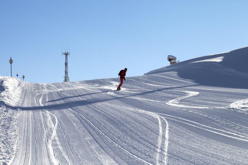 El Snowboarder desciende en la cuesta nevosa del esquí preparada por el snowcat foto de archivo