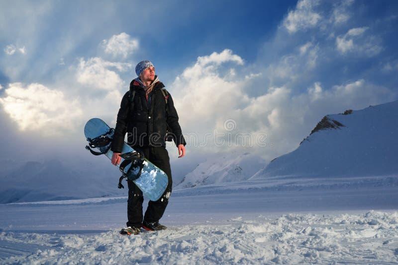 El Snowboarder en el traje negro que se coloca en trackand mira el lado fotos de archivo libres de regalías