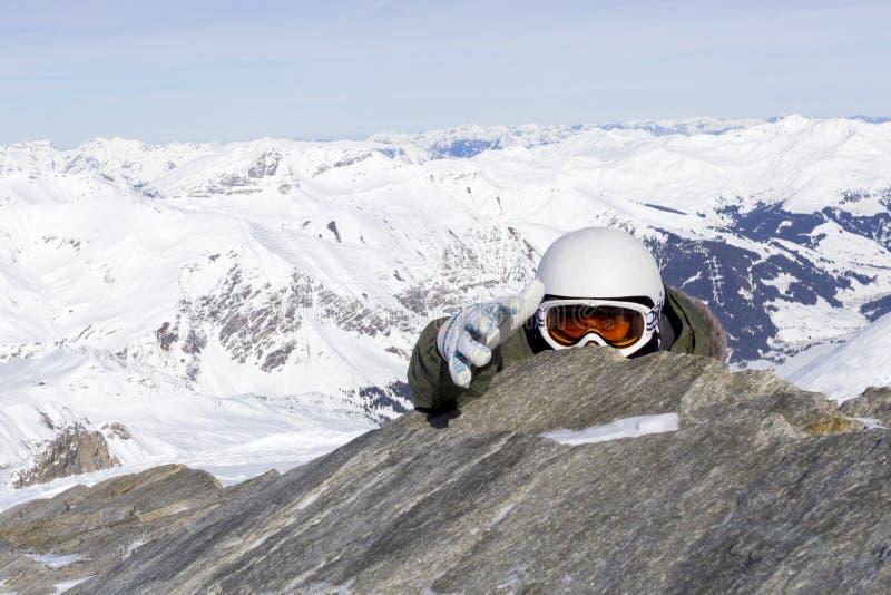 El Snowboarder en gafas anaranjadas del esquí en un casco blanco sube al top y amplía una mano amiga en las montañas de las monta fotos de archivo