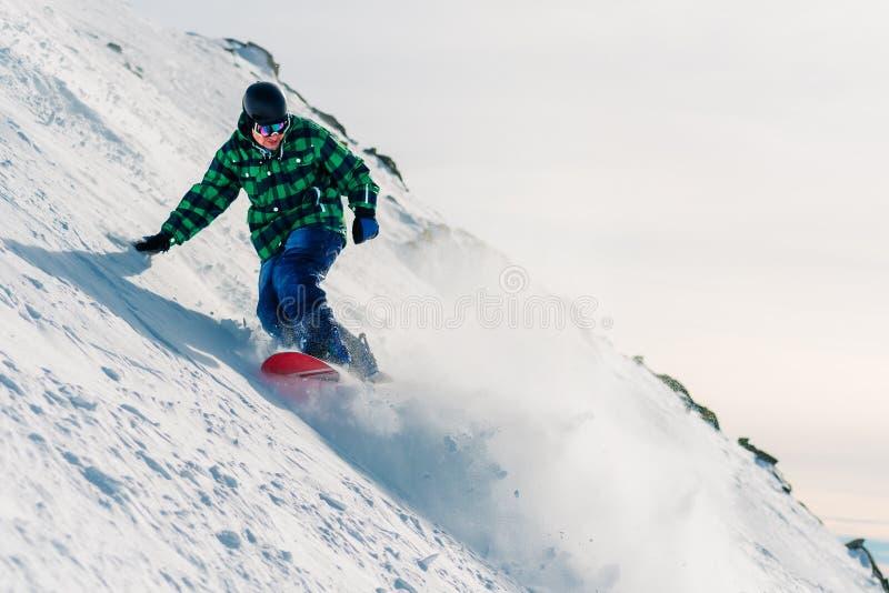 El Snowboarder está montando abajo de la colina de la nieve imagenes de archivo