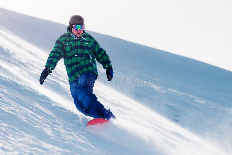 El Snowboarder está montando de la colina de la nieve fotografía de archivo