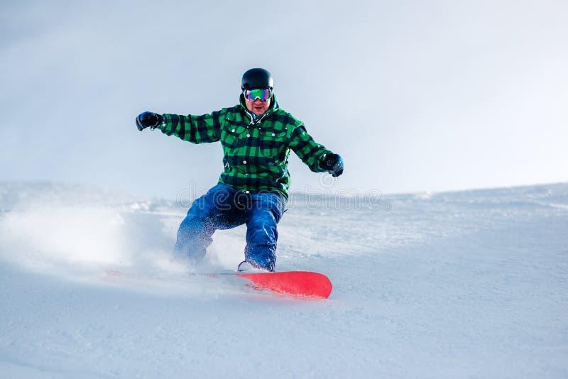 El Snowboarder está montando de la colina de la nieve imagen de archivo libre de regalías