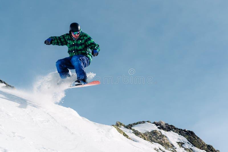El Snowboarder está montando y salto de la colina de la nieve foto de archivo libre de regalías