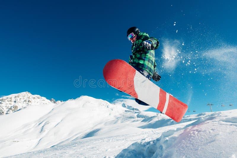 El Snowboarder está saltando con la snowboard del snowhill imagen de archivo libre de regalías