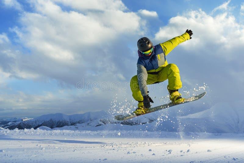 El Snowboarder hace el truco de salto la nieve dispersa pedazos imagen de archivo