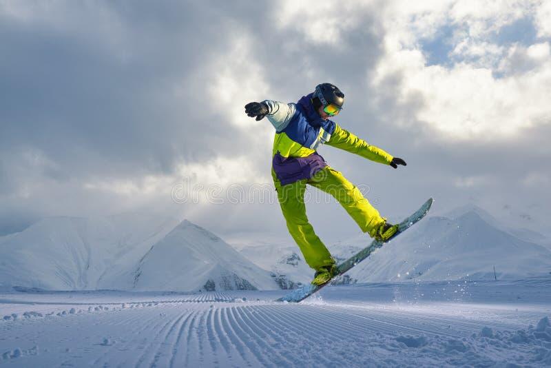 El Snowboarder hace el truco de salto la nieve dispersa pedazos fotografía de archivo