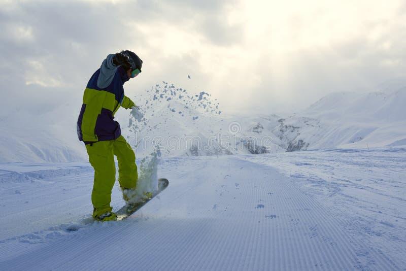 El Snowboarder hace los aumentos del truco el frente del tablero fotos de archivo