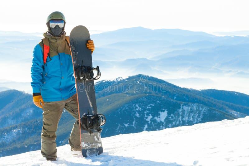 El snowboarder joven que se colocaba al lado de snowboard empujó en nieve con paisaje hermoso en fondo imagen de archivo