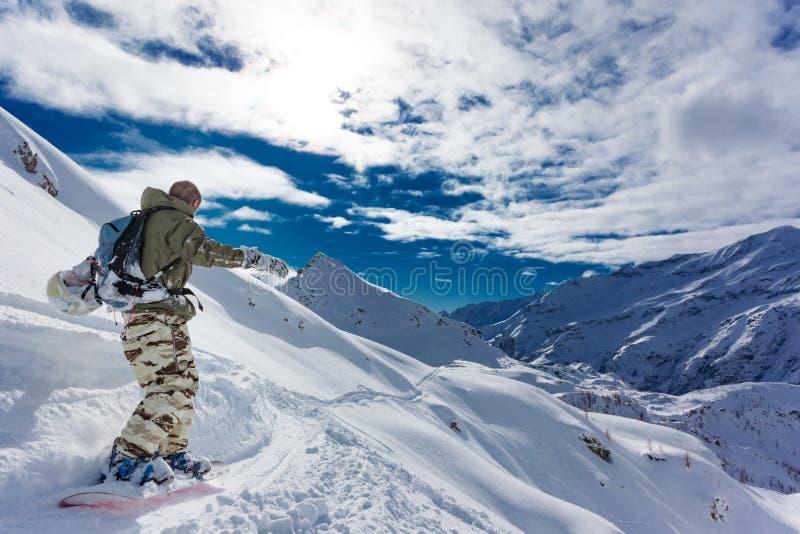 El Snowboarder pasa cuesta abajo un paisaje nevoso de la montaña foto de archivo