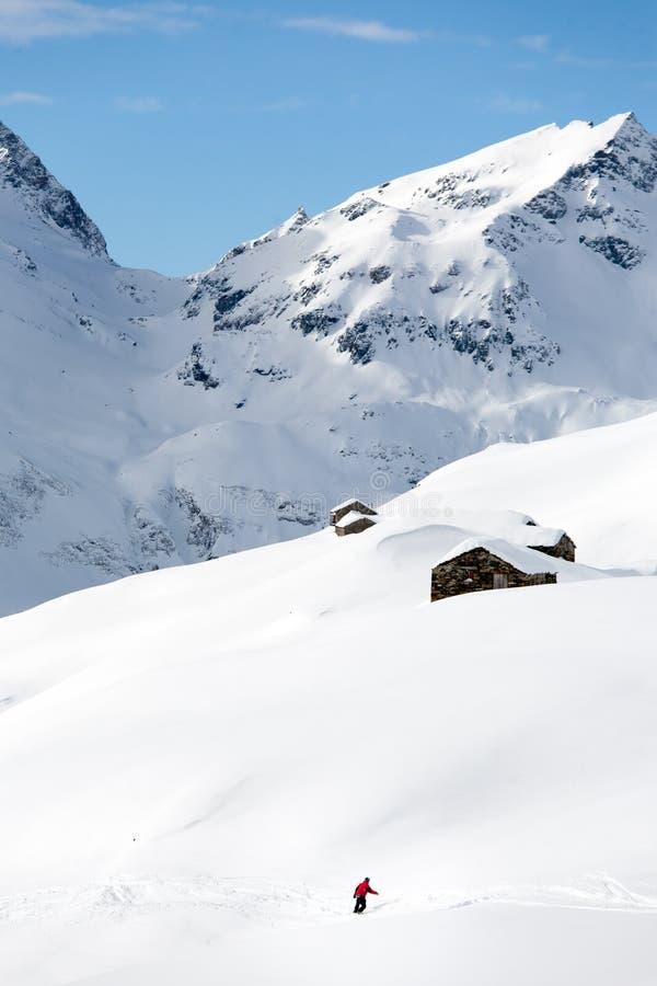 El Snowboarder pasa cuesta abajo un paisaje nevoso de la montaña imágenes de archivo libres de regalías