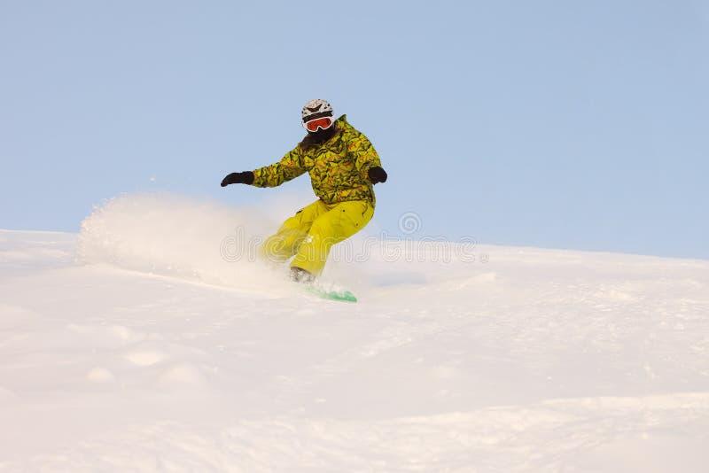 El Snowboarder que hace un lado del dedo del pie talla con el cielo azul profundo en backgro imagen de archivo libre de regalías